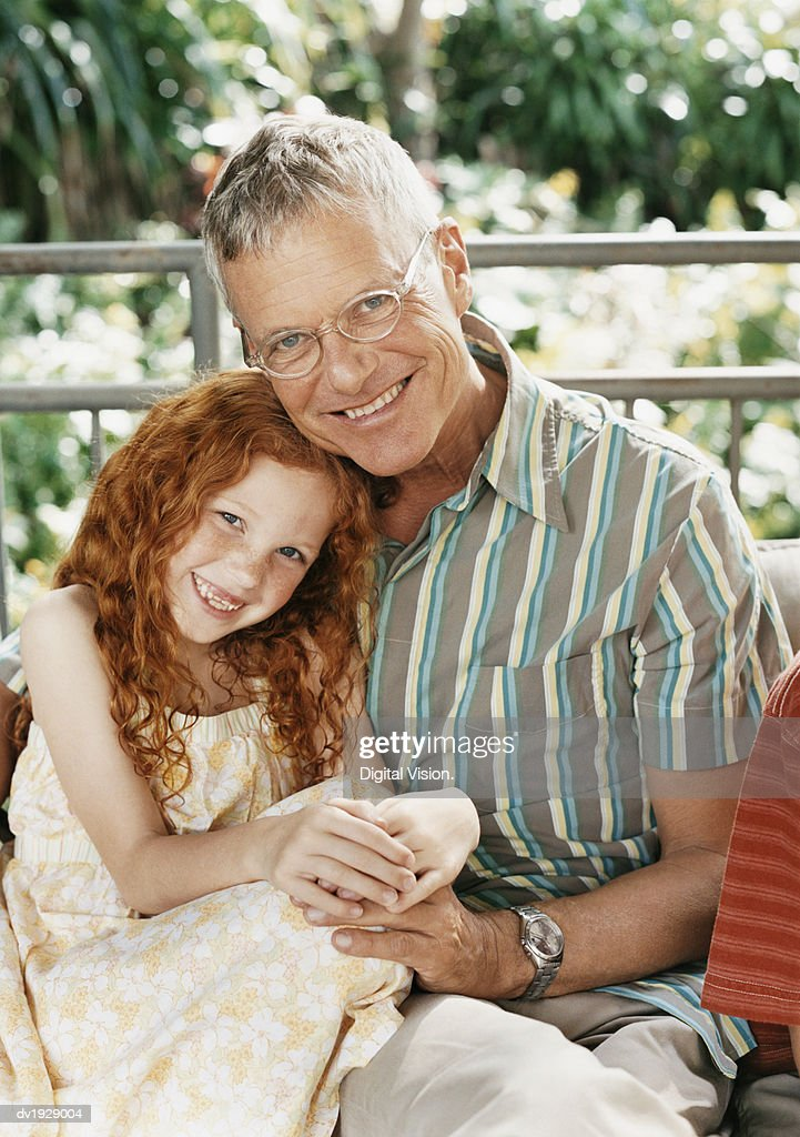 Portrait of a Grandfather and His Granddaughter Sitting Close to Each Other : Stock Photo