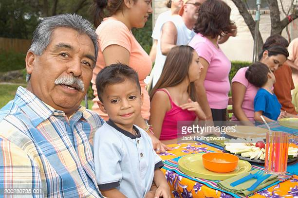 portrait of a grandfather with his grandson in his lap - picnic table stock pictures, royalty-free photos & images