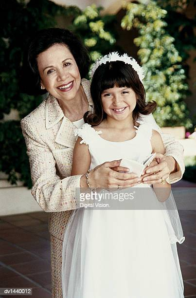 portrait of a grandmother and her young granddaughter in her first communion dress, holding a prayer book - communion stock pictures, royalty-free photos & images