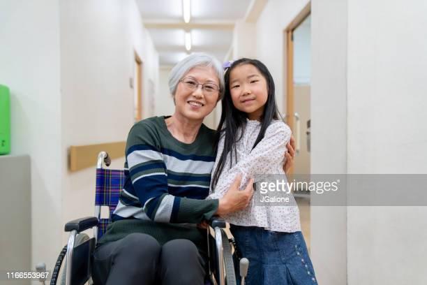車椅子の祖母と病院の孫娘の肖像 - 公共の建物 ストックフォトと画像