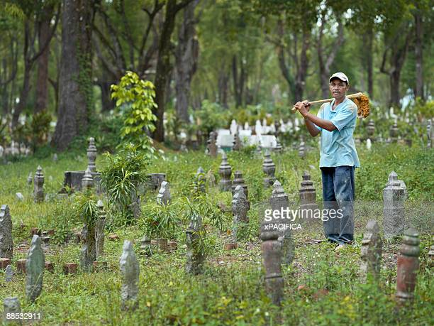 a portrait of a gravedigger standing in a cemetery - 墓堀人 ストックフォトと画像