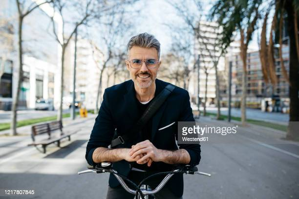 portrait of a gray-haired businessman with bicycle in the city - shoulder bag stock pictures, royalty-free photos & images