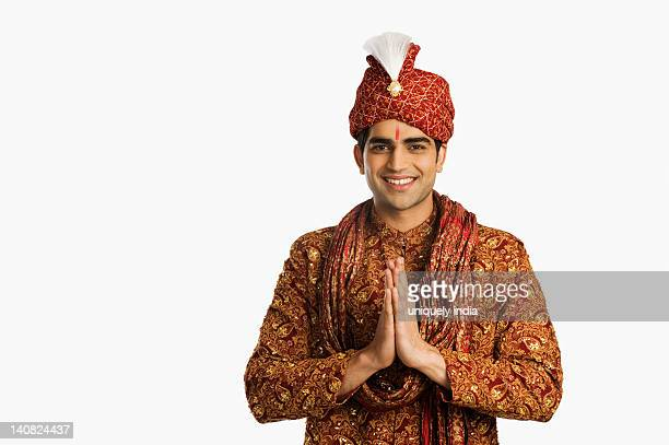 portrait of a groom in traditional wedding outfit standing in prayer position - kurta stock pictures, royalty-free photos & images