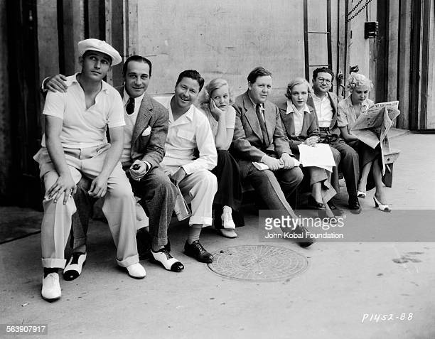 Portrait of a group of actors including Bing Crosby Charles Laughton and Ricardo Cortez sitting outdoors at a studio backlot for Paramount Pictures...