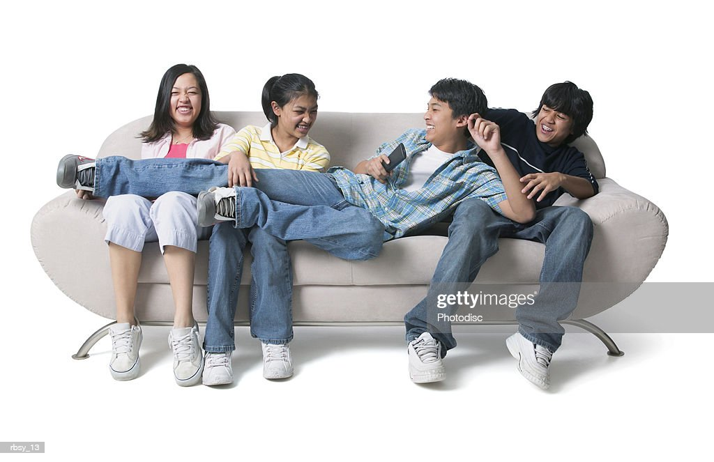 portrait of a group of asian brothers and sisters as they sit on the couch and fight over the remote control : Stockfoto