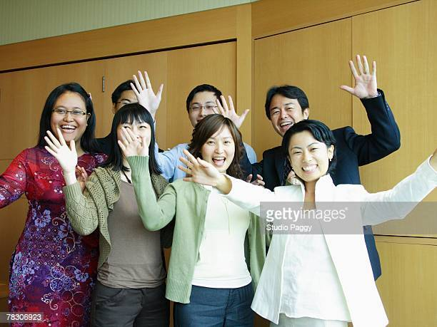 Portrait of a group of business executives waving their hands and cheering in an office