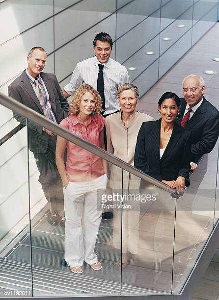 Portrait of a Group of Business People Standing at the Bottom of a Staircase in a Modern Office