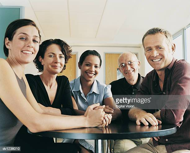portrait of a group of businessmen and businesswomen sitting at a table in an office - next to stock pictures, royalty-free photos & images