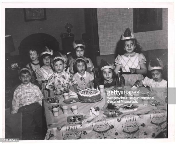 Portrait of a group of children posed behind a cake on a table at a birthday party 1940s Most of them wear feathered headbands Photo by Weegee...