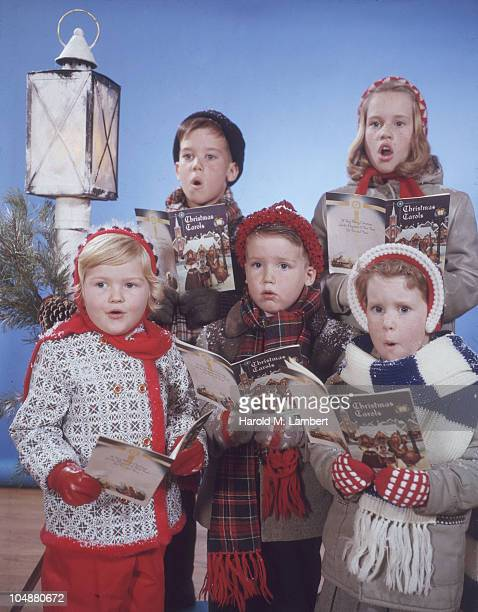 Portrait of a group of five children dressed in winter coats and hats as they sing from a book entitled 'Christmas Carols' 1950s