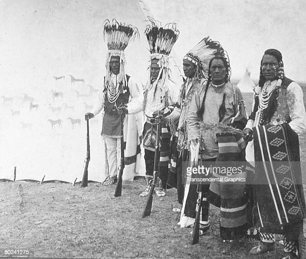 Portrait of a group of five members of a Blackfoot tribe as they pose in ceremonial attire four of them with a rifle in hand outside a tipi late...
