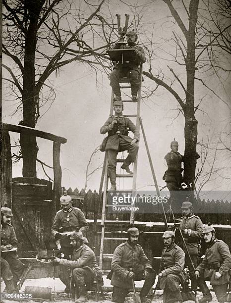 Portrait of a group of German soldiers at an observation post two of them perch on a ladder one with a field spotter periscope and the other with...