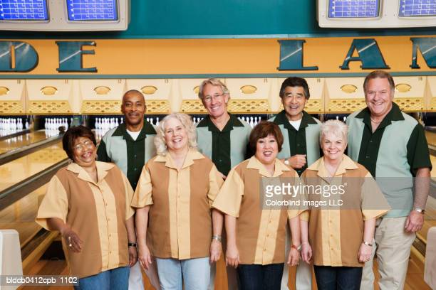 Portrait of a group of mature men and mature women standing in a bowling alley