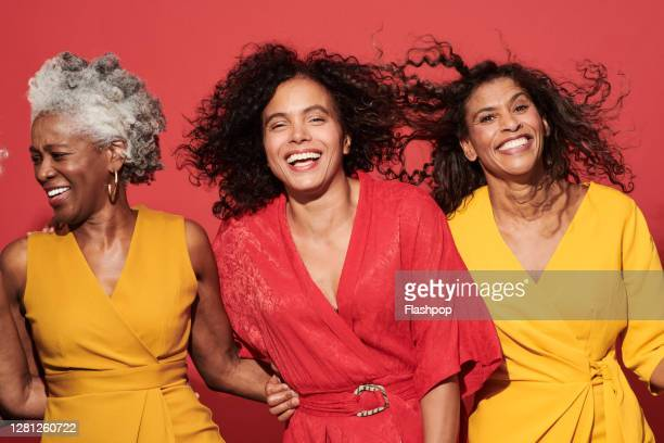 portrait of a group of mature women against a red background - confidence stock pictures, royalty-free photos & images