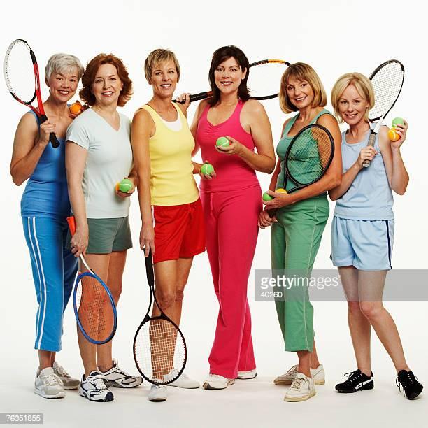 Portrait of a group of mature women holding tennis rackets and tennis balls