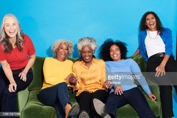 portrait of a group of mature women sitting on a sofa together - female friendship stock pictures, royalty-free photos & images