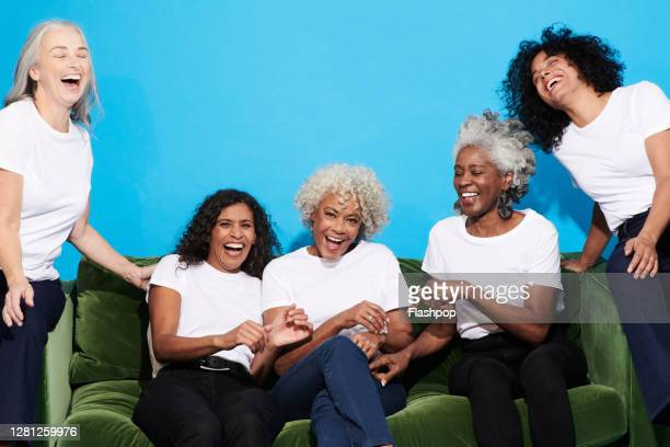 portrait of a group of mature women sitting on a sofa together - happiness stock pictures, royalty-free photos & images