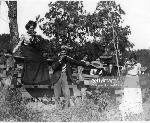 Portrait of a group of men and women as they eat watermelon slice beside a fence near Park Hill Indian Territory circa 1896