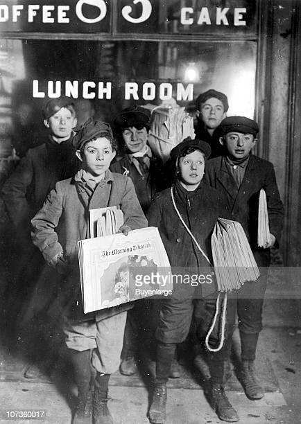 Portrait of a group of newsboys as they pose outside a 'lunch room' in the early hours of the morning near the Brooklyn Bridge New York New York...