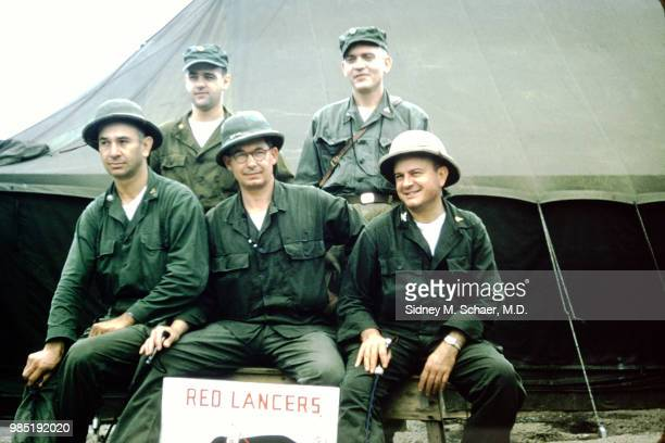 Portrait of a group of soldiers as they pose behind a 'Red Lancers' sign at the 8063rd MASH South Korea January 1952 They are indentified as fore...