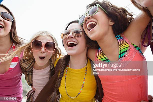 portrait of a group of teenage girls laughing - little girls bent over stock photos and pictures