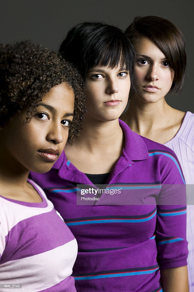portrait of a group of three teenage female friends as they all look seriously at the camera : Foto de stock