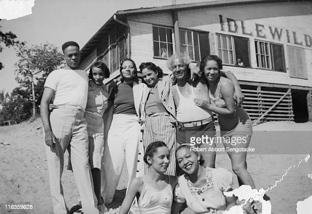 Portrait of a group of unidentified people as they pose on the beach outside the Idlewild Club House Idlewild Michigan September 1938 Idlewild known...