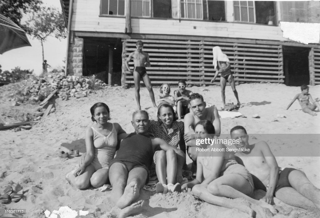 Portrait of a group of unidentified people (friends and/or family members of future newspaper publisher John H. Sengstacke) as they pose on the beach outside the Idlewild Club House, Idlewild, Michigan, September 1938. Idlewild, known as 'the Black Eden,' was a resort community that catered to African Americans, who were excluded from other resorts prior to the passage of the Civil RIghts Act of 1964.