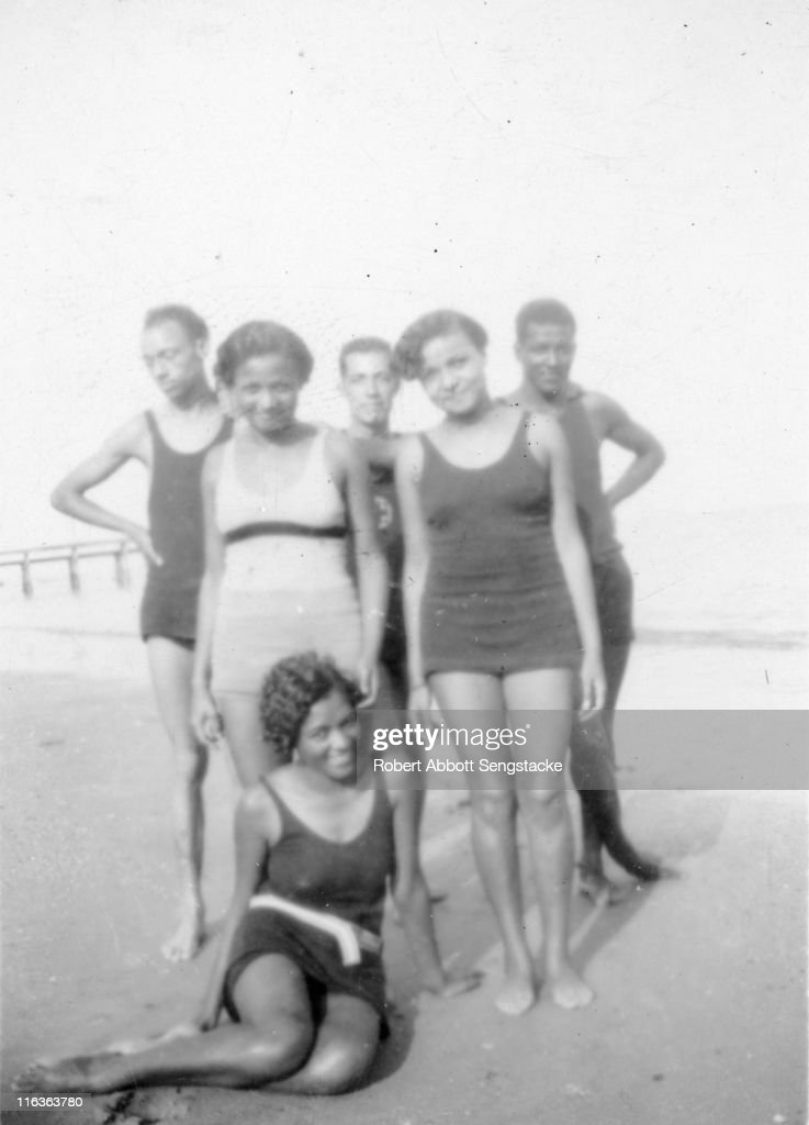 Portrait of a group of unidentified people (friends and/or family members of future newspaper publisher John H. Sengstacke) as they pose on the beach at the edge of Idlewild Lake, Idlewild, Michigan, September 1938. Idlewild, known as 'the Black Eden,' was a resort community that catered to African Americans, who were excluded from other resorts prior to the passage of the Civil RIghts Act of 1964.