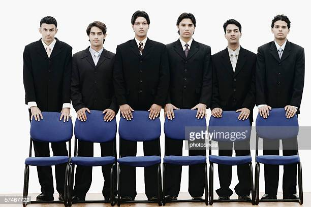 portrait of a group of young men standing behind chairs - abbigliamento da lavoro formale foto e immagini stock