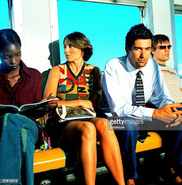 Portrait of a group of young people sitting on a bench in a train