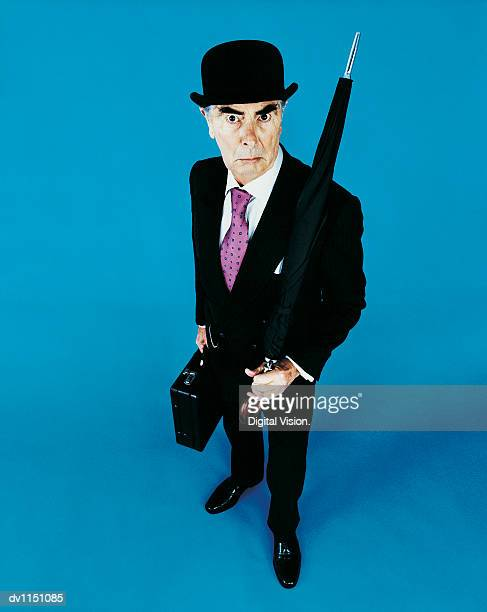 Portrait of a Grumpy Old Businessman With a Bowler Hat, Briefcase and Umbrella