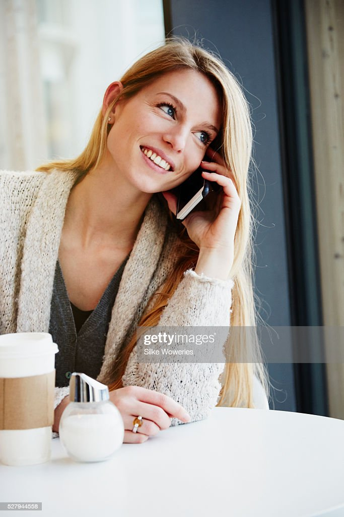 portrait of a handsome adult woman sitting in a cafe talking on her smartphone : Stock Photo