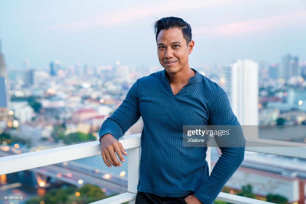 Portrait of a handsome asian man on a rooftop at sunset : Stock Photo