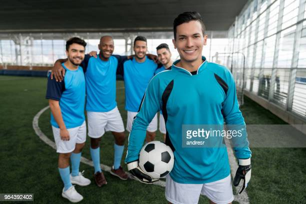 Portrait of a handsome goal keeper holding the soccer ball and his diverse team standing behind