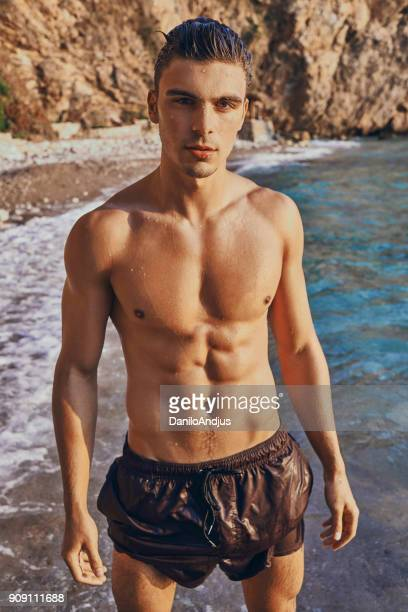 portrait of a handsome male model - muscle men at beach stock photos and pictures