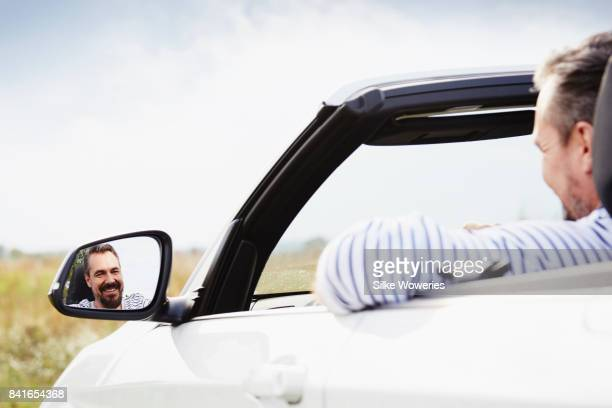 portrait of a handsome man driving through the countryside enjoying the ride
