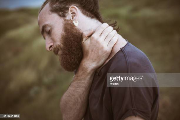 portrait of a handsome man holding his neck - butterflies in the stomach stock pictures, royalty-free photos & images