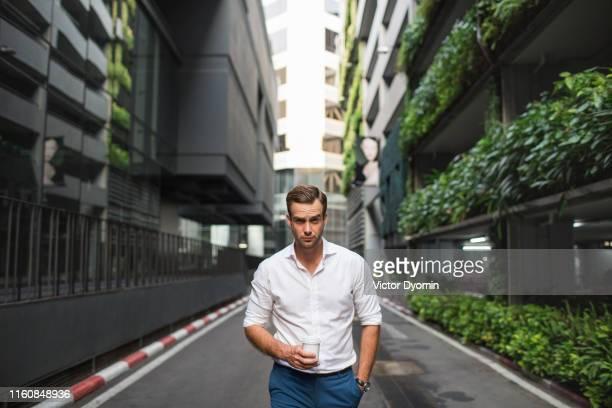portrait of a handsome man walking along a road. - wit hemd stockfoto's en -beelden