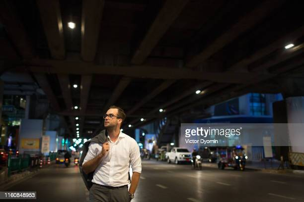 portrait of a handsome man walking at night - editorial stock pictures, royalty-free photos & images