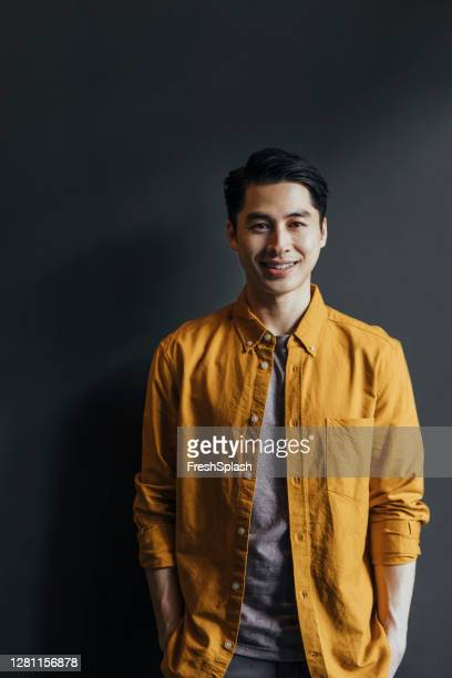 portrait of a handsome young asian man in a yellow shirt, looking at camera - all shirts stock pictures, royalty-free photos & images