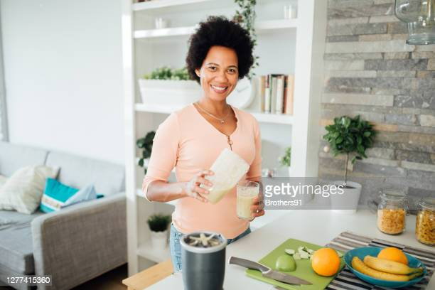 portrait of a happy african american woman preparing a nutritional breakfast at home - 40 44 years stock pictures, royalty-free photos & images