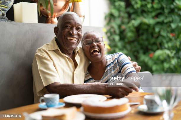 portrait of a happy african senior couple having breakfast - interracial wife stock pictures, royalty-free photos & images