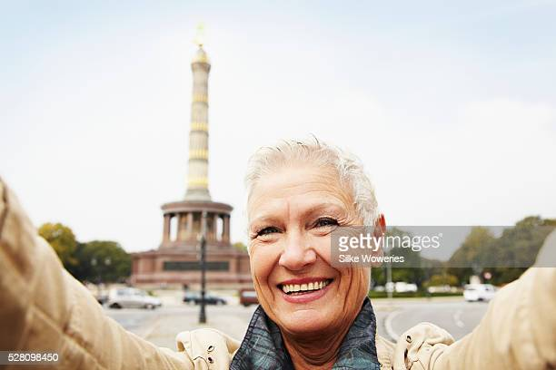 portrait of a happy and content senior woman in front of the Siegess��ule, Berlin.