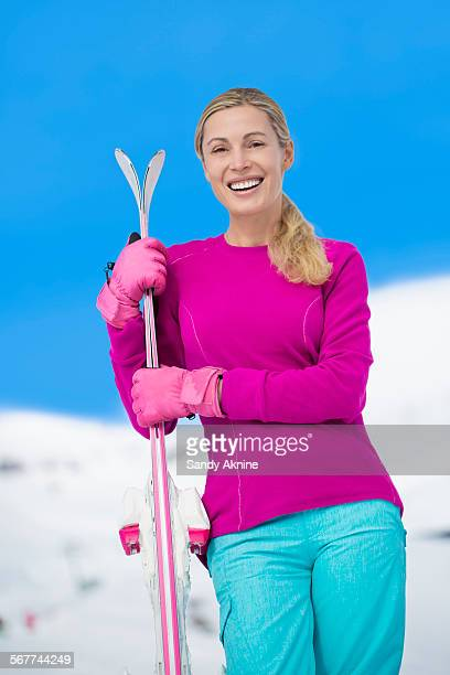 Portrait of a happy beautiful woman holding skis in snow, Crans-Montana, Swiss Alps, Switzerland
