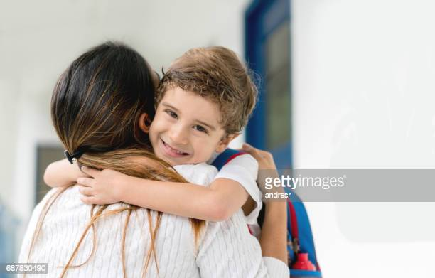 Portrait of a happy boy at school hugging his teacher