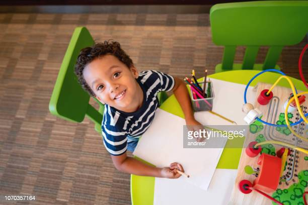 portrait of a happy boy coloring at a kid's airport lounge - coloring stock pictures, royalty-free photos & images
