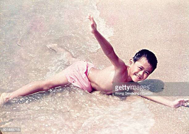 Portrait of a happy boy playing in water at beach
