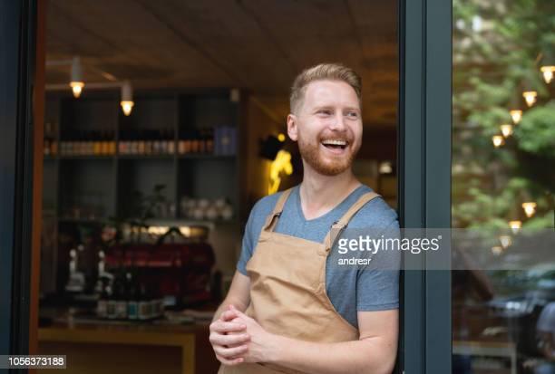 Portret van een gelukkig ondernemer op de deur in een café