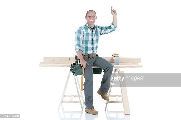 Portrait of a happy carpenter pointing upward